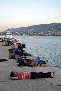 """Μετανάστες είναι ξαπλωμένοι στο λιμάνι της Μυτιλήνης, την Παρασκευή 12 Ιουνίου 2015. Ασφυκτική η κατάσταση στο λιμάνι της Μυτιλήνης από εκατοντάδες παράτυπους μετανάστες και πρόσφυγες που περιμένουν έως και πέντε μέρες να """"συλληφθούν"""" από το Λιμενικό Σώμα και να προωθηθούν στο Κέντρο Υποδοχής της Μόριας. Από εκεί θα πάρουν μετά από μέρες τα απαραίτητα χαρτιά προκειμένου να προωθηθούν στην Αθήνα.  ΑΠΕ- ΜΠΕ/ ΑΠΕ-ΜΠΕ /ΣΤΡΑΤΗΣ ΜΠΑΛΑΣΚΑΣ"""